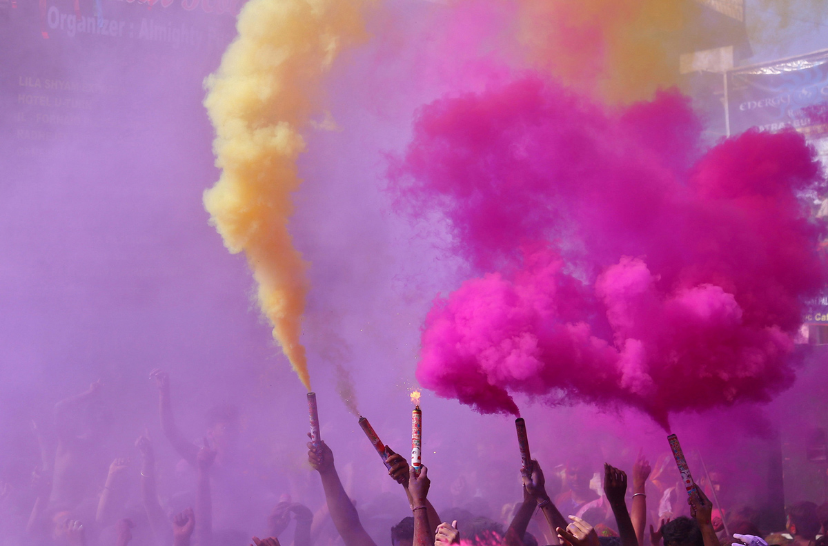 "People release coloured smoke as they take part in ""kapda phaar"" (cloth tearing) Holi, as part of Holi, the Festival of Colours, celebrations in Pushkar"